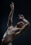 Kroppsbyggare- och remsatema: härligt med den pumpade nakna mannen för muskler som poserar i studion på en mörk bakgrund Royaltyfri Foto