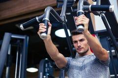 Kroppsbyggare som gör övning på konditionmaskinen i idrottshall royaltyfria bilder