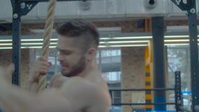 Kroppsbyggare som klättrar ett rep stock video
