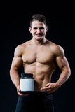Kroppsbyggare som rymmer protein för vassla för etikett för svart plast- krusmellanrum ett vitt och pekar till det med hans hand  royaltyfri fotografi