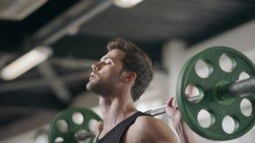 Kroppsbyggare som squatting med skivstången i idrottshall Idrottsman nenmanutbildning i konditionklubba arkivfilmer