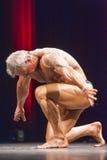 Kroppsbyggare som utför och knäfaller ner på etapp i championshi Fotografering för Bildbyråer