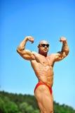 Kroppsbyggare som utomhus böjer hans muskler Arkivfoto