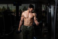 Kroppsbyggare som ?var biceps med hantlar royaltyfria foton