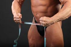 kroppsbyggarehåll som mäter det undressed bandet royaltyfri bild