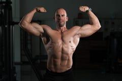 Kroppsbyggarekonditionmodell Posing Double Biceps efter övningar arkivbild
