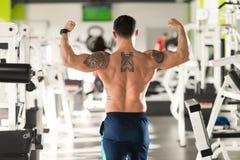 Kroppsbyggarekonditionmodell Posing Double Biceps efter övningar royaltyfri foto