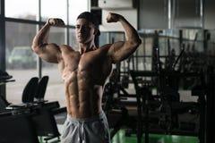 Kroppsbyggarekonditionmodell Posing Double Biceps efter övningar royaltyfria bilder
