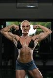 kroppsbyggarekvinnlig som slader muskler royaltyfria foton