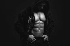Kroppsbyggareman i huven som visar hans torso Arkivbild