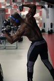 Kroppsbyggareman som poserar i idrottshallen royaltyfri foto