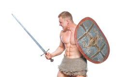 Kroppsbyggareman som poserar med ett svärd och en sköld som isoleras på vit bakgrund Allvarlig shirtless hans mandemonstrering royaltyfri foto