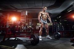 Kroppsbyggaremananseende med skivstången, genomkörare i idrottshall Arkivbilder