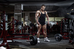 Kroppsbyggaremananseende med skivstången, genomkörare i idrottshall Royaltyfria Foton