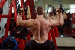 Kroppsbyggaremanlyftande hantlar i idrottshallen arkivfoto