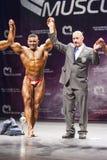 Kroppsbyggaren firar hans seger på etapp med representanten Royaltyfri Bild