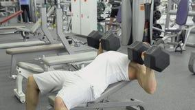kroppsbyggaren gör bänkpress som använder hantlar på idrottshallen Muskulös man som övar i idrottshallen arkivfoto