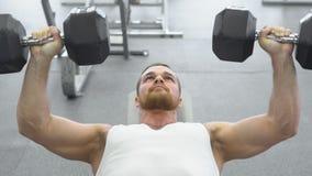 kroppsbyggaren gör bänkpress som använder hantlar på idrottshallen Muskulös man som övar i idrottshallen Royaltyfri Fotografi