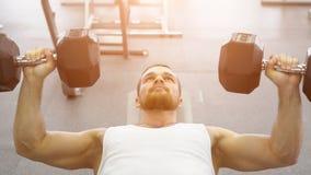 kroppsbyggaren gör bänkpress som använder hantlar på idrottshallen Muskulös man som övar i idrottshallen Royaltyfri Foto