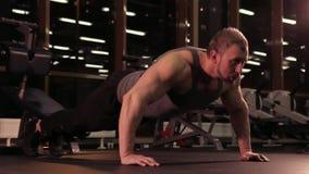 Kroppsbyggaren gör push-UPS i konditionklubban lager videofilmer