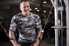 Kroppsbyggaren utarbetar driftig övre övning i idrottshall Royaltyfria Bilder