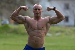 Kroppsbyggaren utförande Front Double Biceps Poses In parkerar arkivfoton