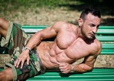Kroppsbyggares nakna torso, pecs, abs som lutar på en bänk Arkivfoto