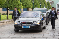 Kroppvakter skyddar den statliga bilen, som flyttar sig i den storslagna slotten i Bangkok Fotografering för Bildbyråer