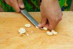 Krossa ett stycke av vitlök på en träskärbräda Arkivbild
