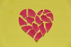 Krossad pappers- hjärta på gul bakgrund broken begreppshjärta Arkivfoto