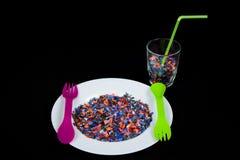 Krossade mångfärgade plast- stycken på den vita plattan och grönt lila för gaffel och glass fullt för sked och av plast- stycken Arkivfoton
