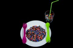 Krossade mångfärgade plast- stycken på den vita plattan och grönt lila för gaffel och glass fullt för sked och av plast- stycken Royaltyfria Bilder