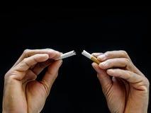 Krossande cigarett för manlig hand på svart bakgrund, begrepp Quitti royaltyfri foto