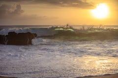 Krossande stenig kustlinje för solnedgångvåg arkivbild