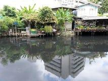 Krottenwijk langs een vuil kanaal stock foto