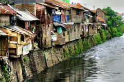 Krottenwijken op rivier, Indonesië Stock Afbeeldingen