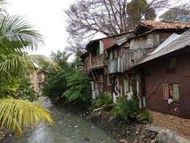 Krottenwijkgebied op riverbank in Djakarta stock foto