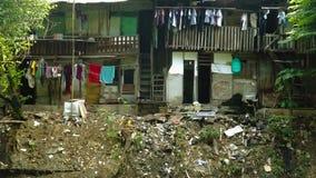 Krottenwijkhuizen op vuile rivieroever stock videobeelden