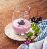 Körsbärsröd yoghurt och mogen körsbär med en kvist av Royaltyfri Foto