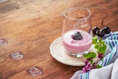 Körsbärsröd yoghurt och mogen körsbär med en kvist av Royaltyfri Bild
