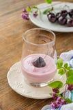 Körsbärsröd yoghurt och mogen körsbär med en kvist av Arkivfoto