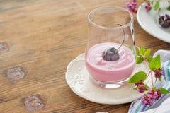 Körsbärsröd yoghurt och mogen körsbär med en kvist av Arkivfoton