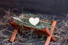 Krubban Jesus och hjärtan av förälskelse gör sammandrag julsymbol Royaltyfria Bilder