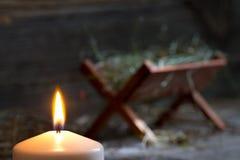 Krubban Jesus och ljus av hopp gör sammandrag julsymbol arkivfoto