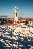 Krucyfiks statua w zimy śnieżnej wsi z wzgórzami na jasnym niebie blisko Koniakow wioski w Beskid Slaski moun i tle Obraz Royalty Free