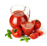 Krug, Glas Tomatensaft und Früchte mit grünen Blättern Stockbilder