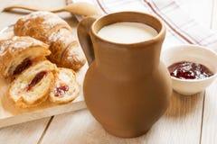 Krug Milch auf einem Hintergrund der Kirschmarmelade und der Hörnchen Lizenzfreie Stockfotos