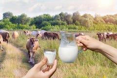 Krug Milch in der Hand und Glas Lizenzfreie Stockbilder