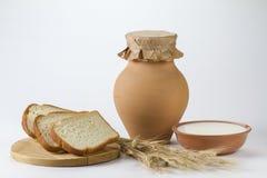 Krug Milch mit frisch gebackenen Weißbrot und den Weizenähren Stockfotografie