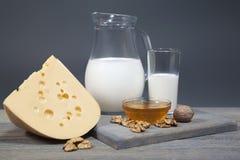 Krug mit Milch, Käse und Honig auf einem hölzernen Brett Stockbilder